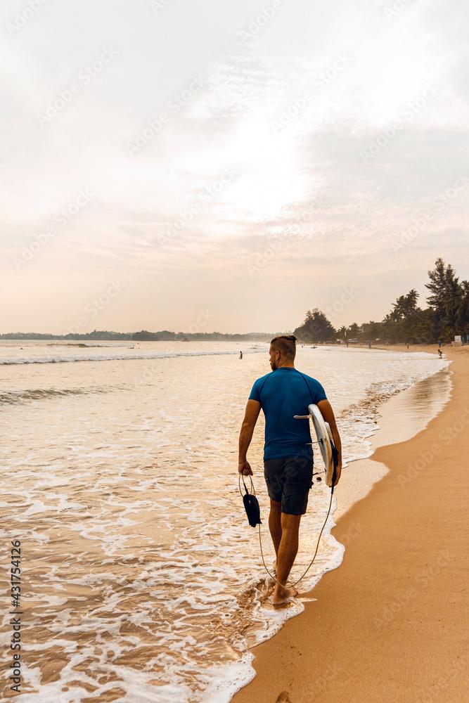Fototapeta Surfer mężczyzna idący z deską po plaży na tle zachodu słońca.