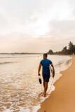 Fototapeta Fototapety z morzem do Twojej sypialni - Surfer mężczyzna idący z deską po plaży na tle zachodu słońca.