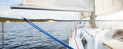 White yacht with full sails running downwind wing-on-wing, sailing after the storm. Close-up view from the deck to the bow. Leisure activity, sport, recreation theme. Glomma river, Oslofjord, Norway