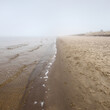 Leinwandbild Motiv Sandy shore of the Baltic sea in a thick white morning fog. Early spring in Latvia. Idyllic rural scene. Nordic walking, recreation, eco tourism, environmental conservation concepts