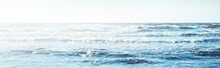A View From The Baltic Sea Shore At Sunset. Clear Blue Evening Sky, Waves And Water Splashes. Idyllic Seascape. Latvia
