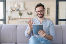 Friendly Young Caucasian Man Having Video Call On Digital Tablet, Communicating With Relatives, Girlfriend, Doctor, Friends Online At Home. Social Distance, Isolation And Lockdown Concept
