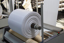 The Resulting Polypropylene Sleeve For The Manufacture Of Bags Is Wound On Large Reels. Drum For Winding Sleeves Of Woven Polypropylene Yarns. PP Bag Production Line