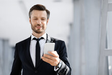 Happy Entrepreneur Reading Emails From Business Partners In Airport