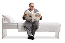 Mature Man In A Robe Relaxing On A Bed With A Newspaper