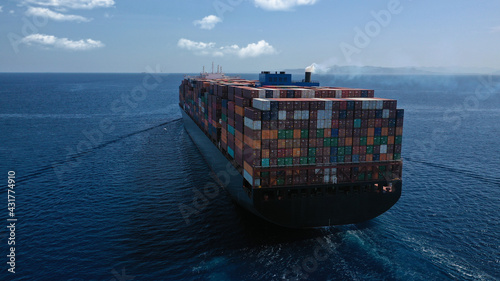 Aerial drone photo of huge container carrier tanker ship cruising deep blue open ocean sea - fototapety na wymiar