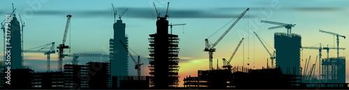 Foto lot of hoisting cranes above buildings at sunset