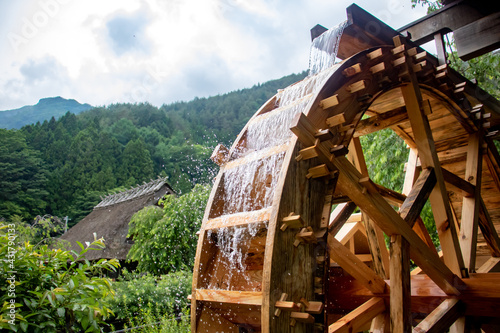 Fotografiet The mill wheel rotates under a stream of water, open air museum at village with