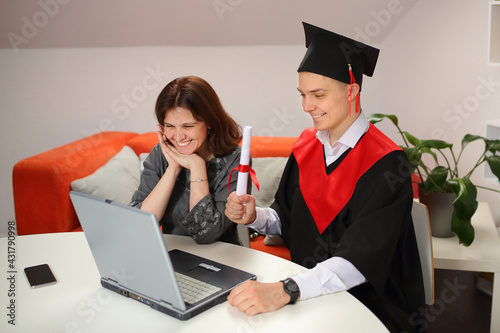Obraz Mother looks at Laptop screen with happy students in graduation gown and a square cap during Virtual graduation ceremony - fototapety do salonu