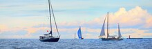 Blue Sloop Rigged Sailboat, Vintage Wooden Two Mast Yacht (yawl) And Other Yachts Anchored Off The Coast Of England Under The Colorful Sky After A Thunderstorm. Dramatic Seascape