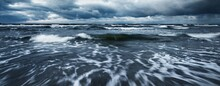 Storm Clouds Above The Baltic Sea In Winter, Long Exposure. Dramatic Sunset Sky, Waves And Water Splashes. Dark Seascape. Germany