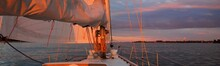 White Yacht Sailing In The Baltic Sea At Sunset. Dramatic Sky With Glowing Clouds Reflecting In The Water. Setting Sun. Epic Seascape. Travel Destinations, Cruise, Sport And Recreation Concepts