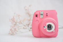 Pink Modern Instant Camera On A White Background And With A Sprig Of Dry Flowers