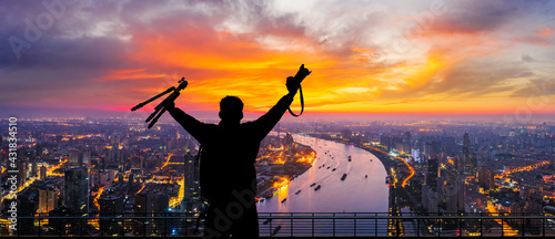 Photo Young photographer standing on the observation deck overlooking the Shanghai city skyline at sunrise