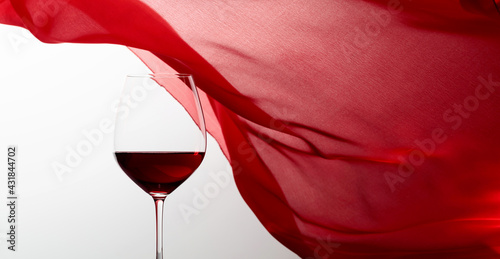 Obraz Glass of red wine on a background of waving red curtain. - fototapety do salonu