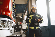 Male Firefighter With Tablet In Uniform On Car Background