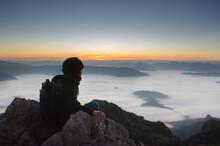 Man Sitting On Mountain Top And Contemplating The Sunrise, Doi Phamon, ChiangRai, Thailand.