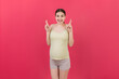 Leinwandbild Motiv Cheerful young pregnant woman holding fingers crossed, waiting pregnancy isolated on colored background in studio. lifestyle pregnancy concept