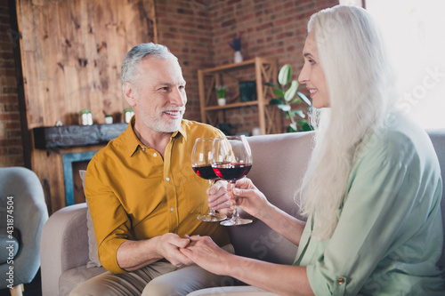 Obraz Portrait of attractive cheerful couple sitting on sofa drinking wine valentine day at loft industrial interior home indoor - fototapety do salonu