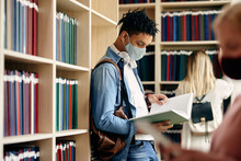 Black University Student With Face Mask Reading From A Book While Learning In Library.