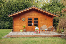 Small Wooden Hut In The Garden. Garden Shed With A Chair In Front Of The Door. Nice Wooden Hut In The Countryside In A Small Forest