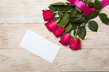 Red Rose Flowers On Wood Table Background With White Blank Envelope. Invitation, Greeting Template For Flat Lying Design, Top View
