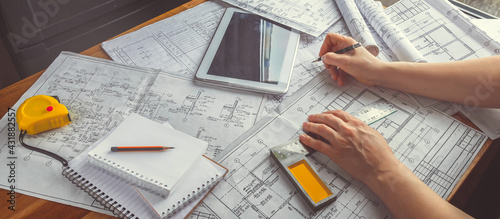 Architect works remotely from home in quarantine, lockdown covid 19 coronavirus. Remote work, stay home, new normality, social distance. Architect design working drawing sketch plans blueprints