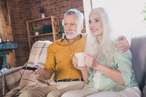 Obraz Photo of old grey haired retired pensioner couple sit couch drink tea watch tv indoors inside house home - fototapety do salonu