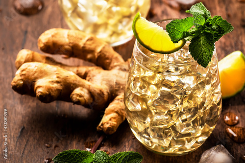 Obraz Ginger Ale Alcoholic Cocktail with Beer, Lime, Lemon and Mint Leaves in glaass on wooden table - fototapety do salonu