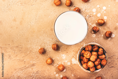 Obraz Hazelnut nut milk in glass beige table background. Non dairy alternative vegan milk. Healthy vegetarian diet food and drink - fototapety do salonu