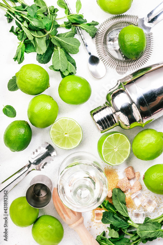 Obraz Mojito cocktail preparing ingredients: lime, mint, ice and bar tools, white background, top view - fototapety do salonu