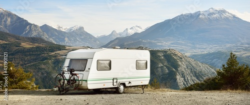 Fotografie, Obraz Caravan trailer, bicycle and car parked on a mountaintop with a view on French Alps near lake Lac de Serre-Poncon