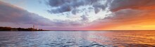 Baltic Sea At Sunset. Dramatic Sky With Glowing Clouds Reflecting In The Water. Lighthouse In The Background. Setting Sun. Epic Seascape. Abstract Natural Pattern, Texture, Background, Concept Image