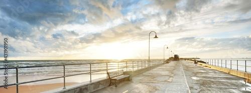 Fotografia An empty pedestrian walkway (promenade) to the Baltic sea at sunset