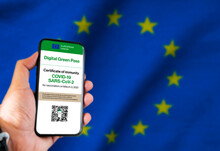 The Digital Green Pass Of The European Union With The QR Code On The Screen Of A Mobile Held By A Hand With A Blurred EU Flag In The Background