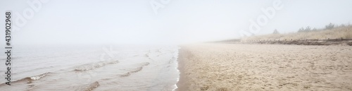Sandy shore of the Baltic sea in a thick white morning fog. Early spring in Latvia. Idyllic rural scene. Nordic walking, recreation, eco tourism, environmental conservation concepts - fototapety na wymiar