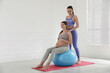 Leinwandbild Motiv Trainer working with pregnant woman in gym. Preparation for child birth