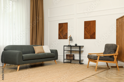 Fototapeta Beautiful sofa with cushions and armchair in living room. Interior design obraz