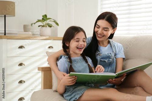 Young mother and her daughter reading book on sofa at home, space for text