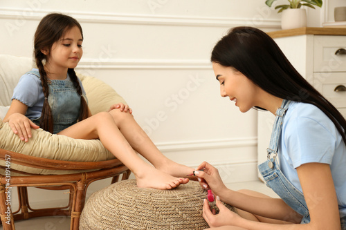 Young mother applying polish on daughter's nails at home