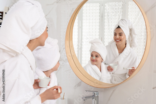 Young mother applying mask onto daughter's face near mirror in bathroom