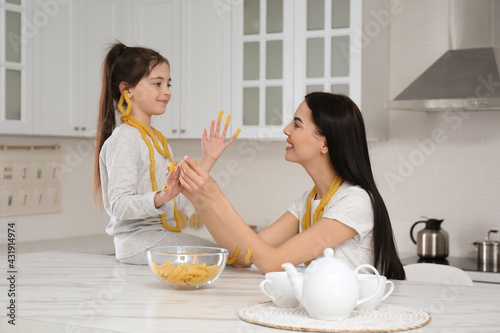Young mother and her daughter with necklaces made of pasta having fun in kitchen