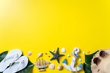 Summer Beach Design Concept With Shells, Hat, Slipper On Yellow Background.