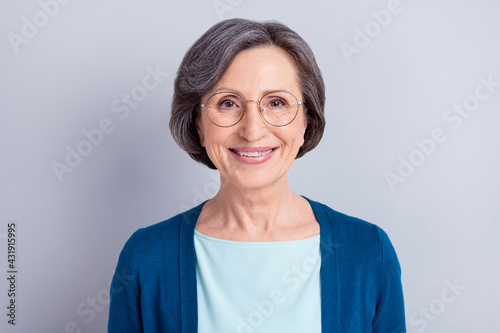 Fototapeta Photo of sweet charming age woman wear blue cardigan glasses smiling isolated green color background obraz