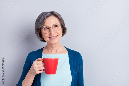 Obraz Photo portrait of elder business woman drinking coffee dreamy curious isolated on grey color background - fototapety do salonu