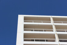Low Angle Shot Of A White Building With Empty Balconies Against The Blue Sky