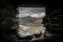 Beautiful View Of Mount Snowden Landscape Through Window Of Abandoned Miners Bothie Cottage In Dinorwic Slate Quarry North Wales. Derelict Miners House With Blue Lake Of Water And Dramatic Sky Clouds.