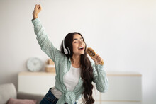 Happy Indian Lady With Headphones Dancing To Music And Singing Song, Using Hairbrush As Mic At Home