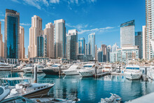 Small Yacht And Motor Boats Parking At The Port Near Dubai Marina Mall With Row Of High Skyscrapers Residential Buildings And Hotels