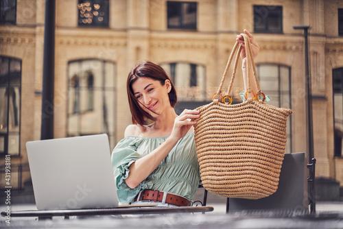 Obraz Girl showing bag on video call - fototapety do salonu